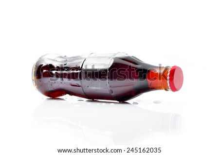 Bottle of cola with ice on a white background