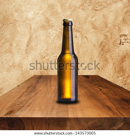 Bottle of cold beer on wood table - stock photo