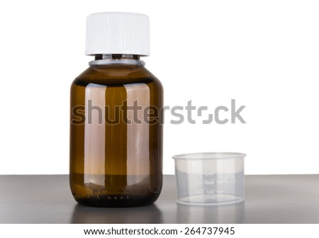 Bottle of cough syrup and volumetric capacity isolated on white background