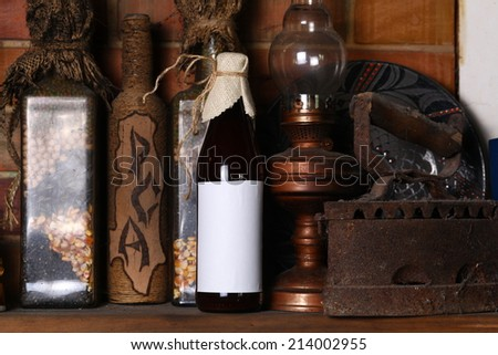 Bottle of craft beer with a blank label template standing on a fireplace shelf with various vintage objects - stock photo