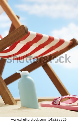 Bottle of cream lotion under deckchair on beach - stock photo