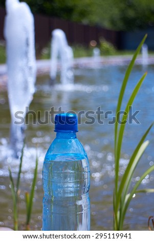 bottle of drinking water against the source water fountain - stock photo