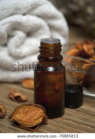 Bottle of essence oil, potpourri and towel - stock photo