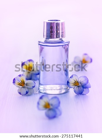 Bottle of essential aromatic oil surrounded by fresh flower - stock photo