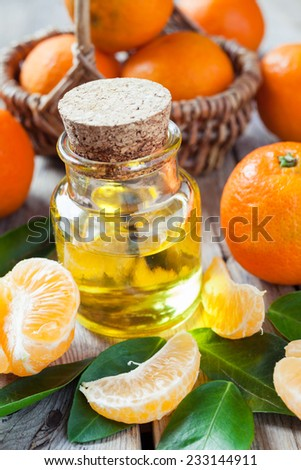 Bottle of essential citrus oil and ripe tangerines in basket on old wooden kitchen table. - stock photo