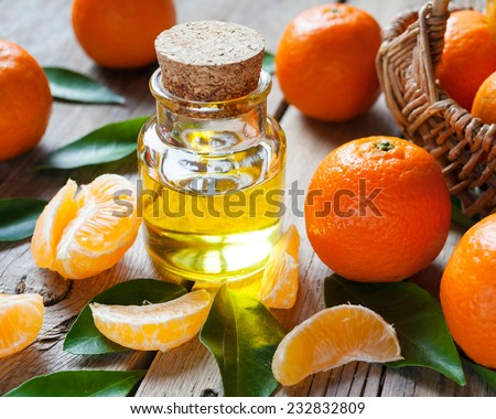 Bottle of essential citrus oil and ripe tangerines with leaves on old wooden kitchen table. - stock photo