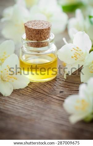 Bottle of essential jasmine oil and white jasmin flowers. - stock photo