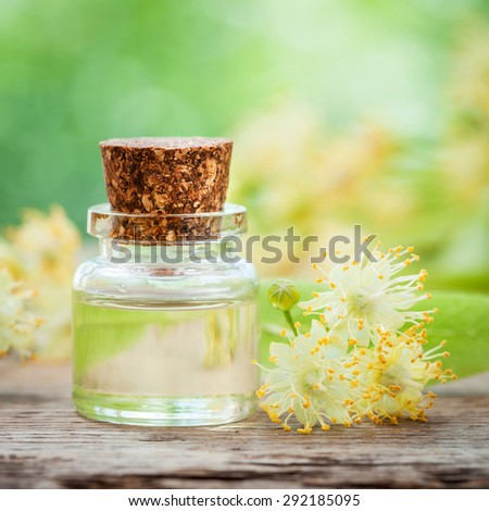 Bottle of essential linden oil and yellow lime flowers. - stock photo