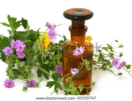 Bottle of essential oil and flowers isolated on white background
