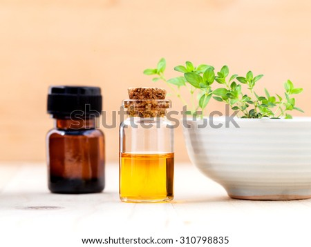 Bottle of essential oil and lemon thyme  leaf  on wooden background. - stock photo