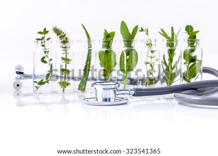Bottle of essential oil with herb holy basil leaf, rosemary,oregano, sage,basil and mint with stethoscope on white background. - stock photo