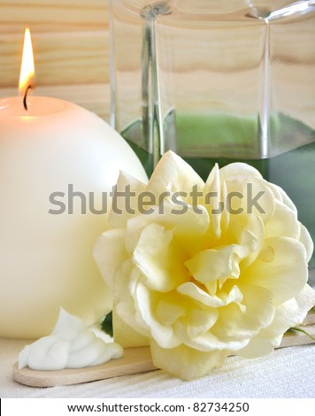 bottle of essential oil with nourishing mask and a rose - stock photo