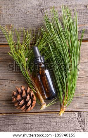 Bottle of fir essential oil on wooden board - stock photo