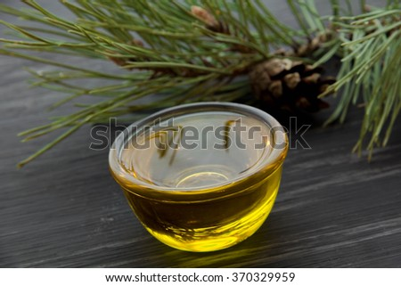 Bottle of fir tree essential oil black wooden background close up - stock photo