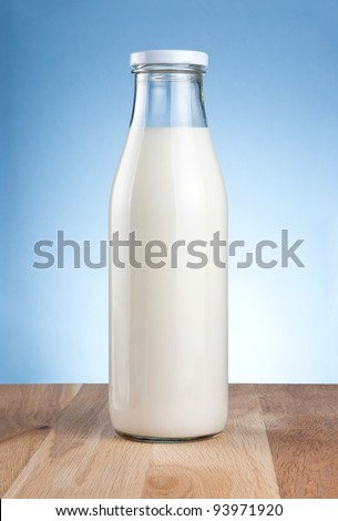 Bottle of fresh milk is wooden table on a blue background - stock photo