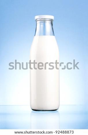 Bottle of fresh milk isolated on a blue background - stock photo