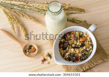 Bottle of fresh milk with Oat and whole wheat grains flake on wooden table - stock photo