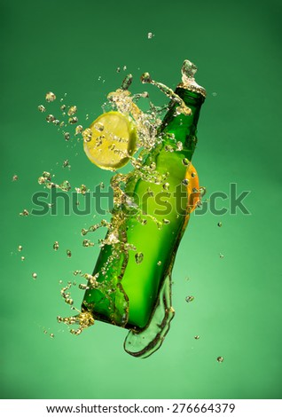 Bottle of fruit beer with splash around on green background. - stock photo