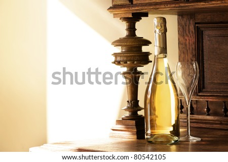 Bottle of golden champagne and wineglass on background of antique furniture.