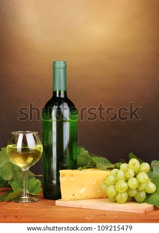 Bottle of great wine with glass and cheese on wooden table on brown background