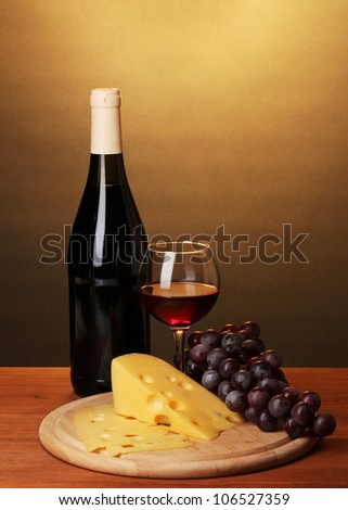 Bottle of great wine with wineglass and cheese on wooden table on brown background