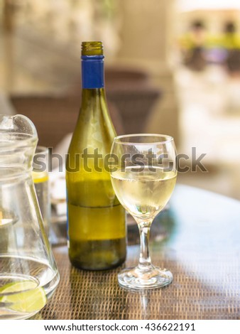 Bottle of Half Empty White Wine on a Wicker Table with a Glass and Jug of Water - stock photo