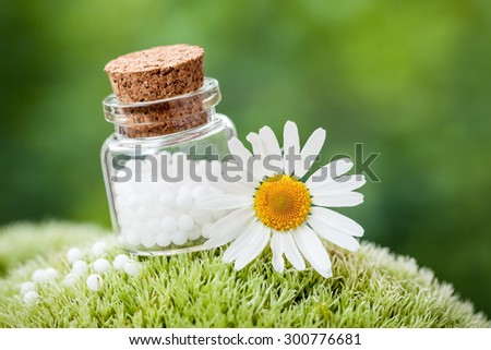 Bottle of homeopathy globules and daisy flower on green moss. - stock photo