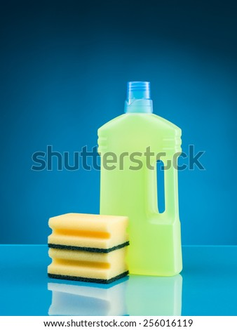 bottle of liquid detergent and sponges against blue background - stock photo