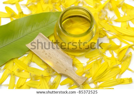 bottle of massage oil a with herbal salt and leaf on yellow flower peals - stock photo