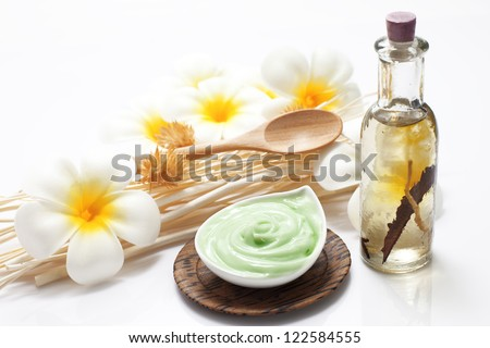 Bottle of massage oil and massage cream arranged with reeds and flowers isolated on white background - stock photo