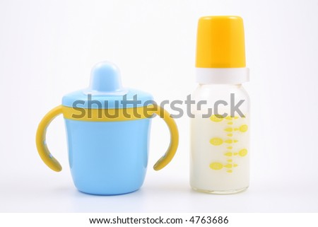 bottle of milk and baby cup - baby stuff - stock photo
