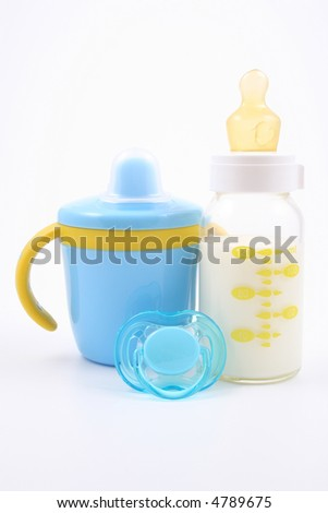 bottle of milk and pacifier - baby stuff - stock photo