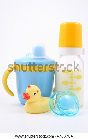 bottle of milk baby cup pacifier and yellow duck - baby stuff - stock photo