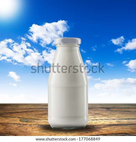 Bottle of milk on wood table - stock photo