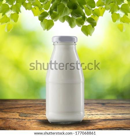 Bottle of milk on wood table - stock photo