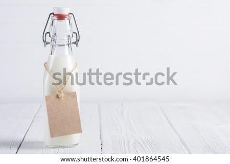 Bottle of milk with blank paper tag on rope on white painted wooden table still life - stock photo