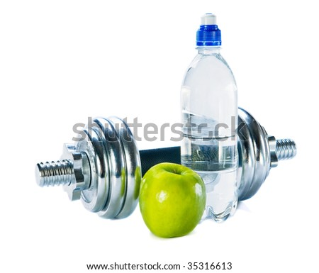 Bottle of mineral water, dumbbells  and green apple isolated over white background