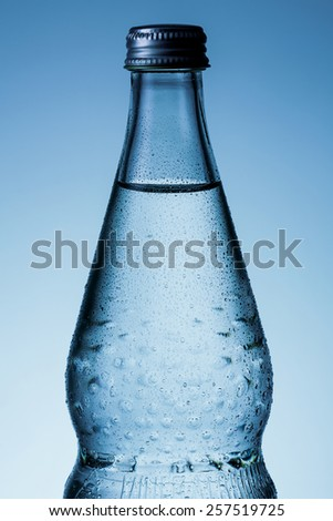 Bottle of mineral water with dew drops - stock photo