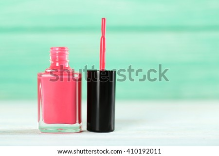 Bottle of nail polish on a wooden table - stock photo