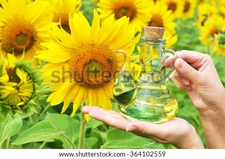 Bottle of oil against sunflowers - stock photo