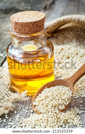 bottle of oil sesame seeds in sack on wooden rustic table - stock photo
