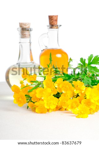 bottle of oil with rapeseed flower, on a canvas background - stock photo