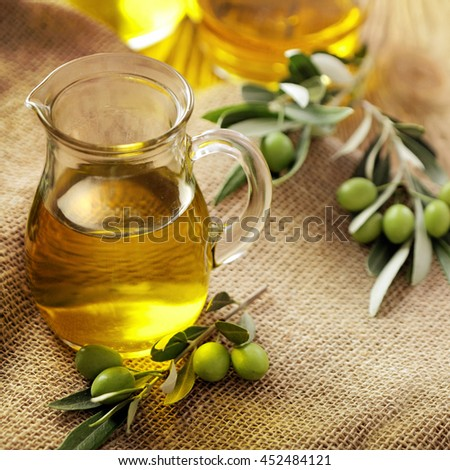 bottle of olive oil and green olives on wooden table - stock photo