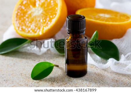 Bottle of orange essential oil for aromatherapy on a brown stone background. - stock photo