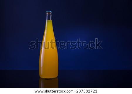 bottle of orange juice on a dark background - stock photo
