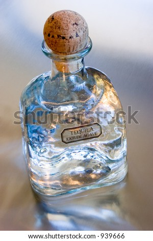 Bottle of Patron Silver Tequila on a reflective metal surface. - stock photo