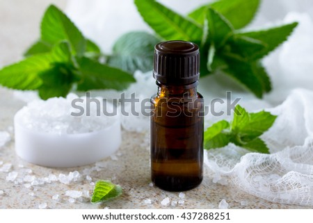 bottle of peppermint essential oil for aromatherapy on a brown stone background. - stock photo