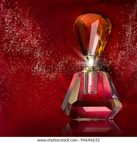 bottle of perfume on a dark red background - stock photo