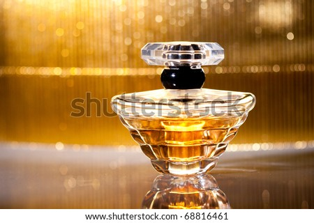 Bottle of perfume with reflection on gold - stock photo