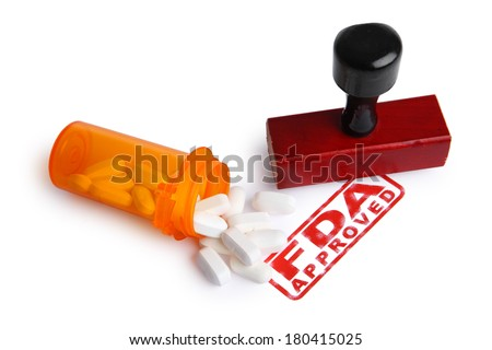 Bottle of Pills and a FDA APPROVED rubber stamp - stock photo
